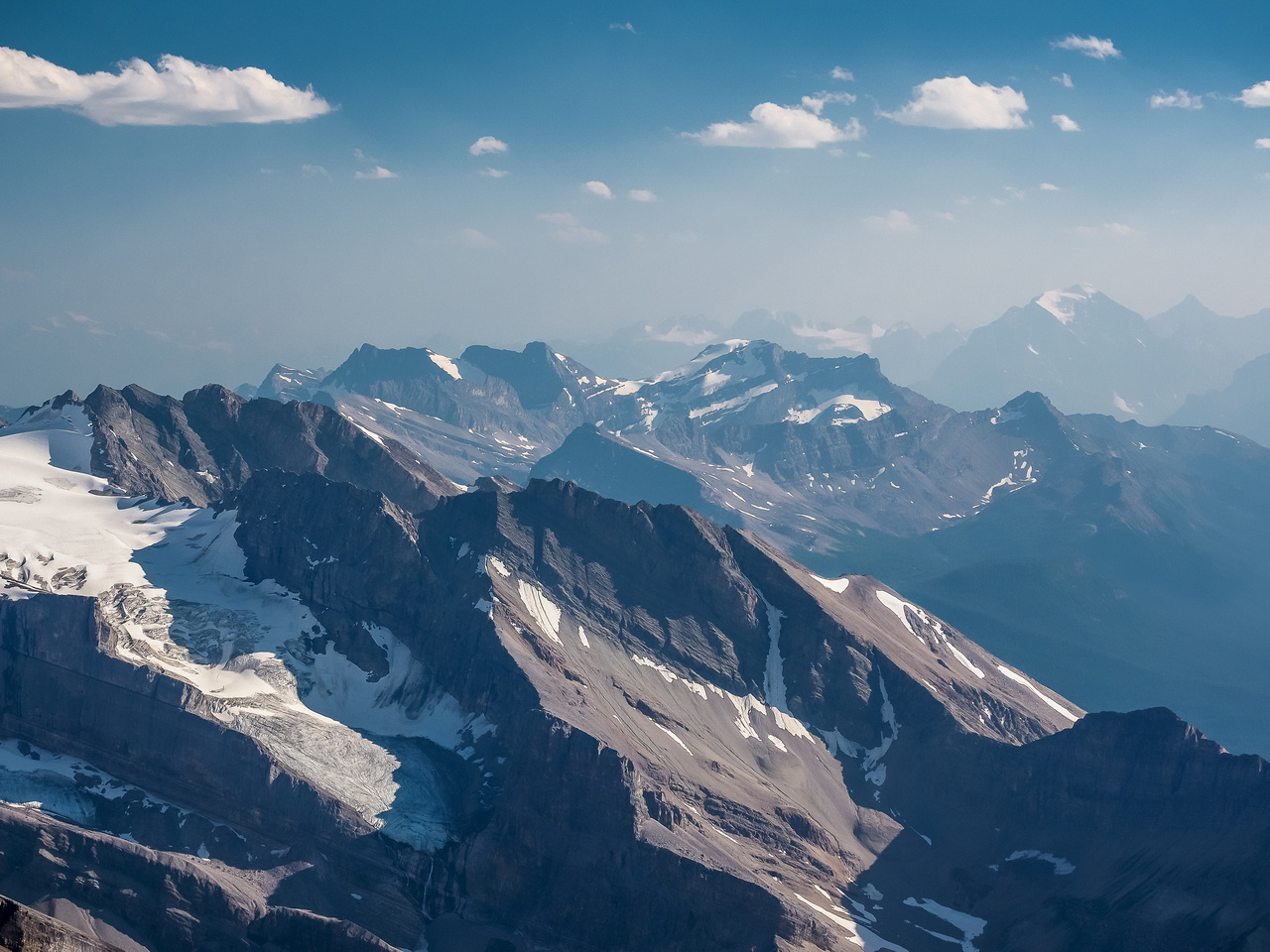 Looking over Cyclone Mountain (L) towards Richardson, Pika and Ptarmigan in the Skoki area and Mount Temple in the smoky haze at distant right.