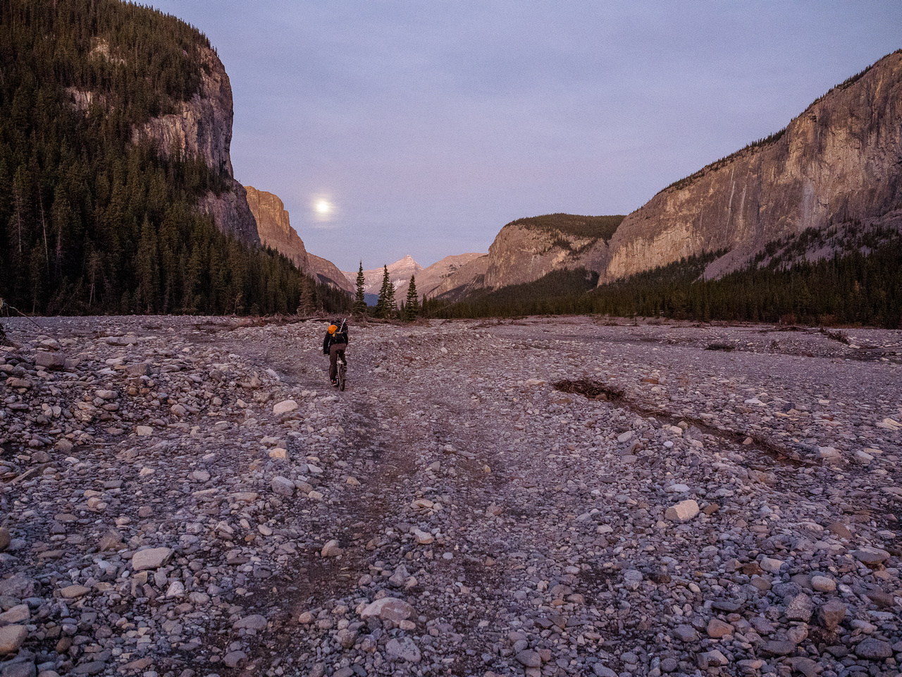 Biking up a surreal landscape along the Ghost River with a very bright moon providing any light we might still need