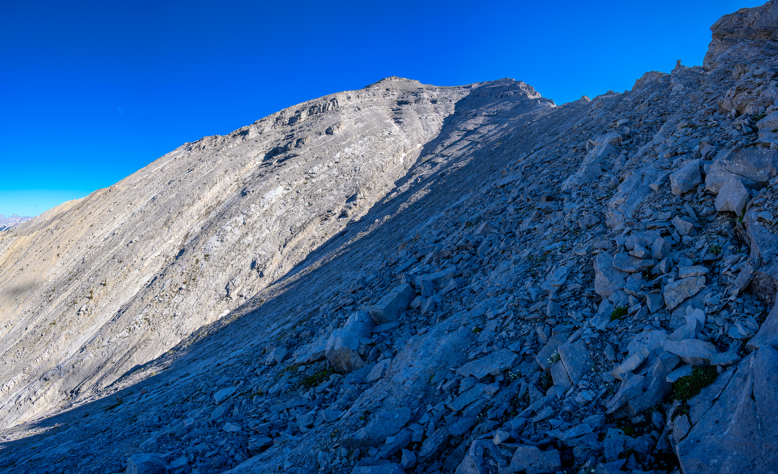 Rather than dealing with slabs and difficult terrain I stay under the ridge on climber's left.