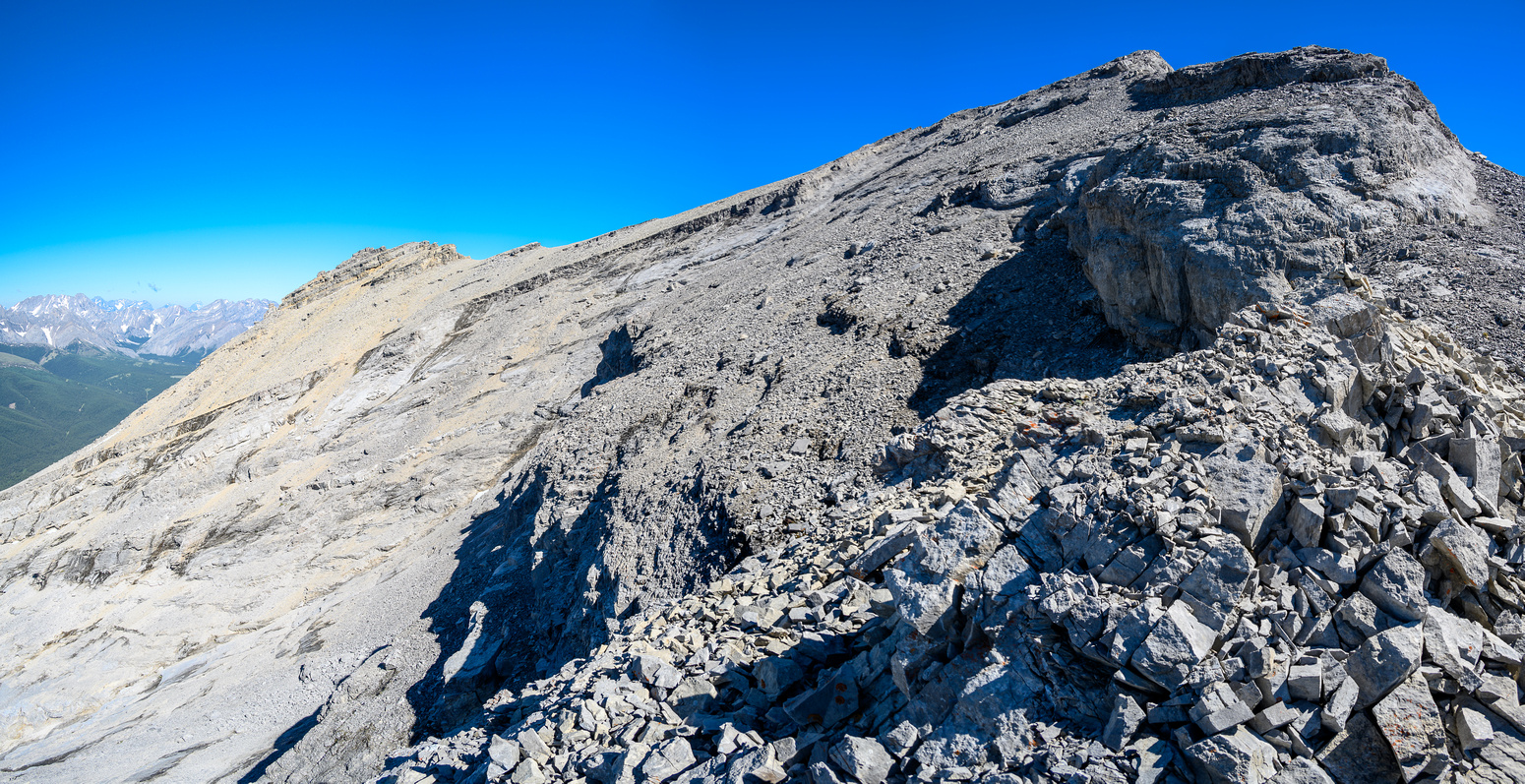 After a long traverse on slabs there is routefinding up the ridge proper to the false summit.