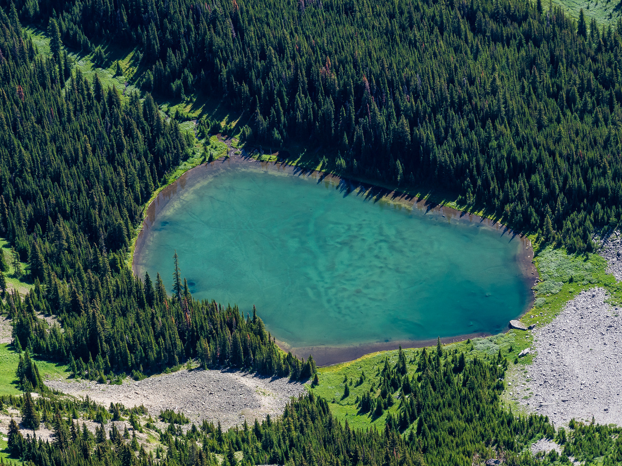 A vibrant tarn sits under the east face of the Opal Range.