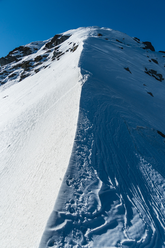 Looking back at the steep snow descent from the false summit down towards the true one.
