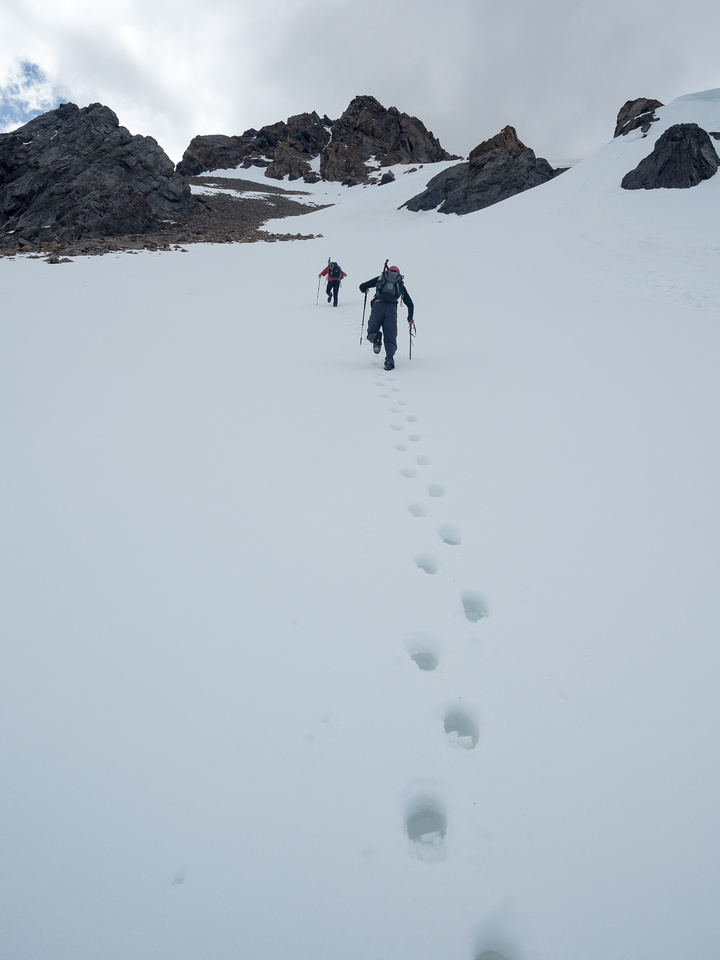 I follow Phil and Geoff up crusty snow to the upper summit block.