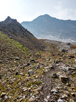 There is a beaten path in the scree that makes the route obvious but does require hiking footwear or you might be slipping around quite a bit.