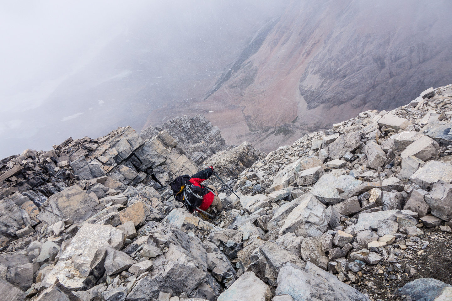 Descending the summit block in a snow squall. Note the loose rocks and steep slabby terrain.