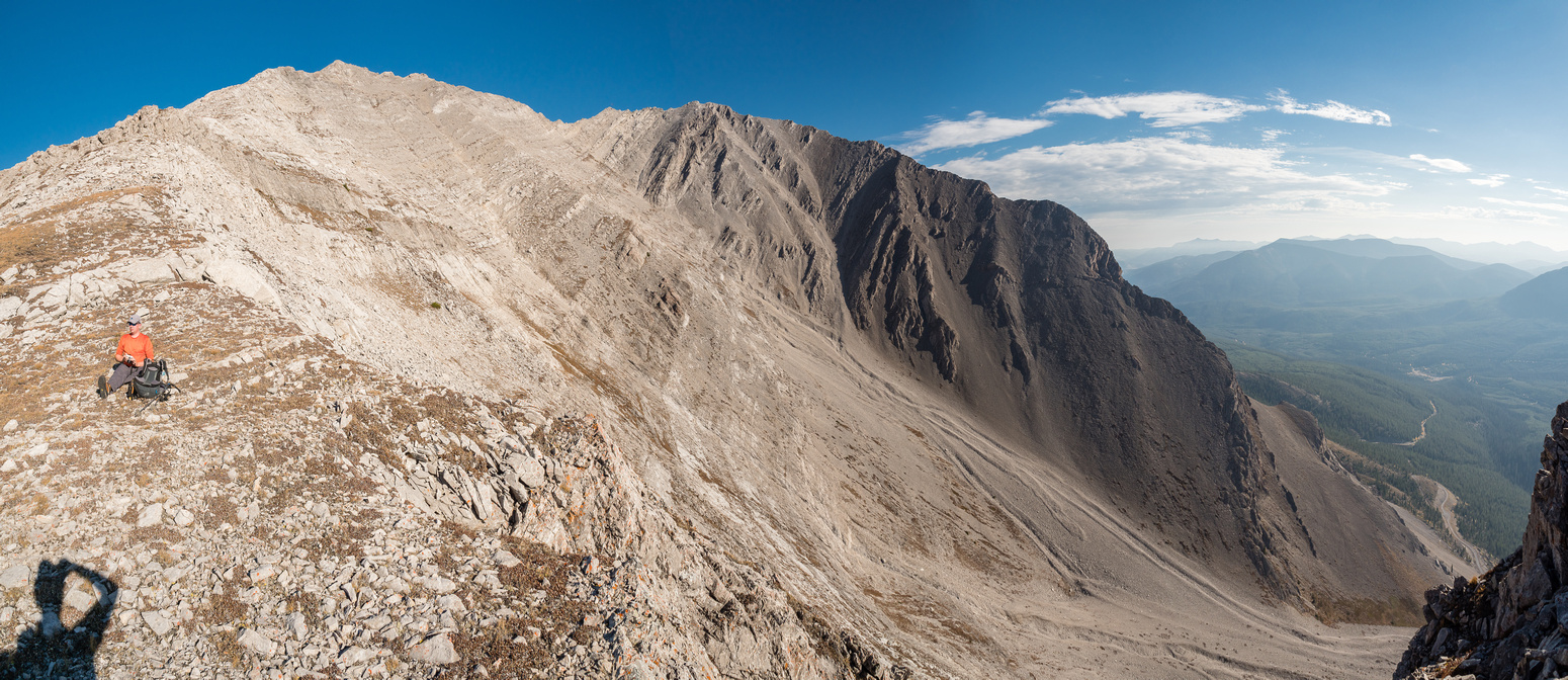 Taking a break on the south ridge. Summit at left, high point at center with the huge slabby scree bowl in between.