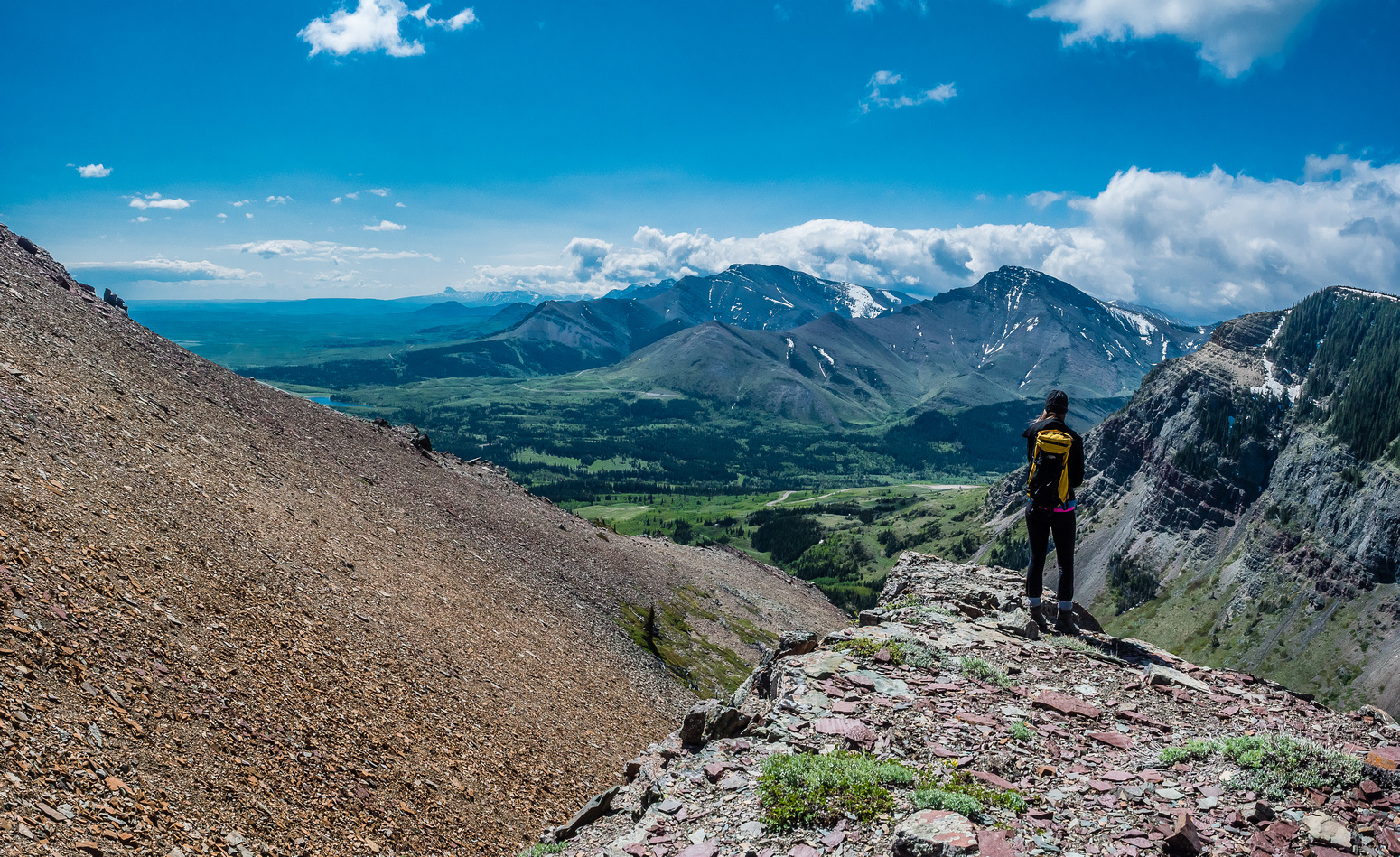 Kaycie enjoys the views towards Pincher Ridge (c) with Drywood Mountain at left. Chief Mountain in Montana is barely visible in the far distance at left.