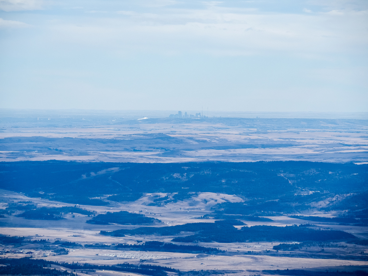The city of Calgary is visible across the plains to the east.