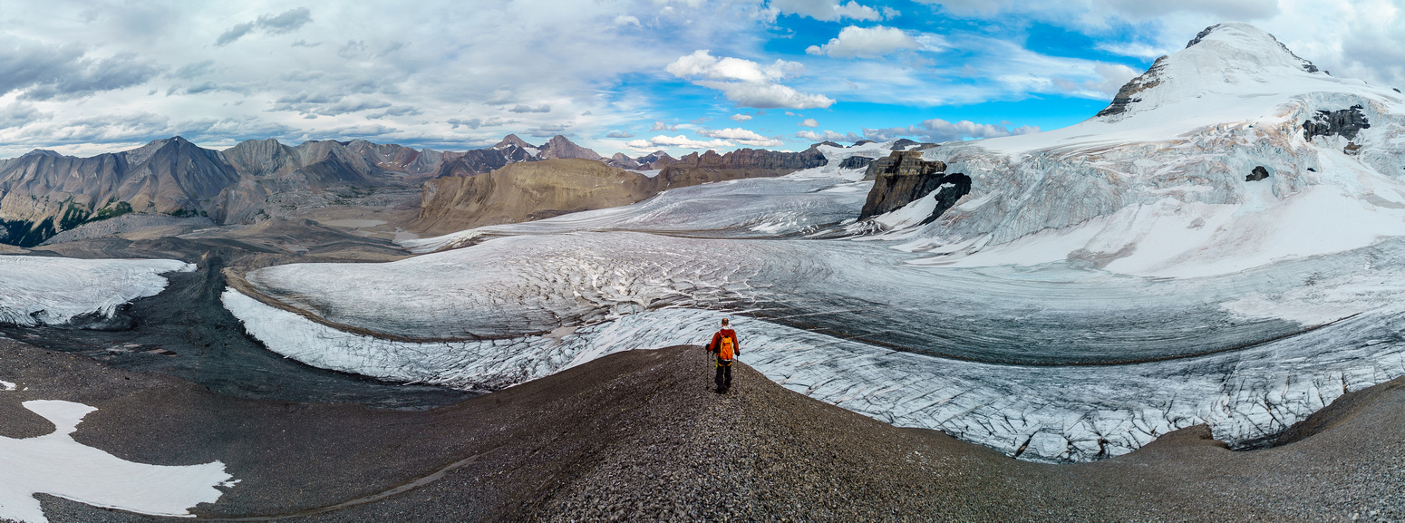 Ben descends the scree ridge to the main lower glacier, which has melted out considerably this day already.