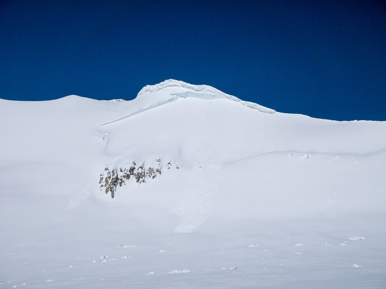 The massive cornice may not look like much from here but that fracture line is at least 20 feet high!