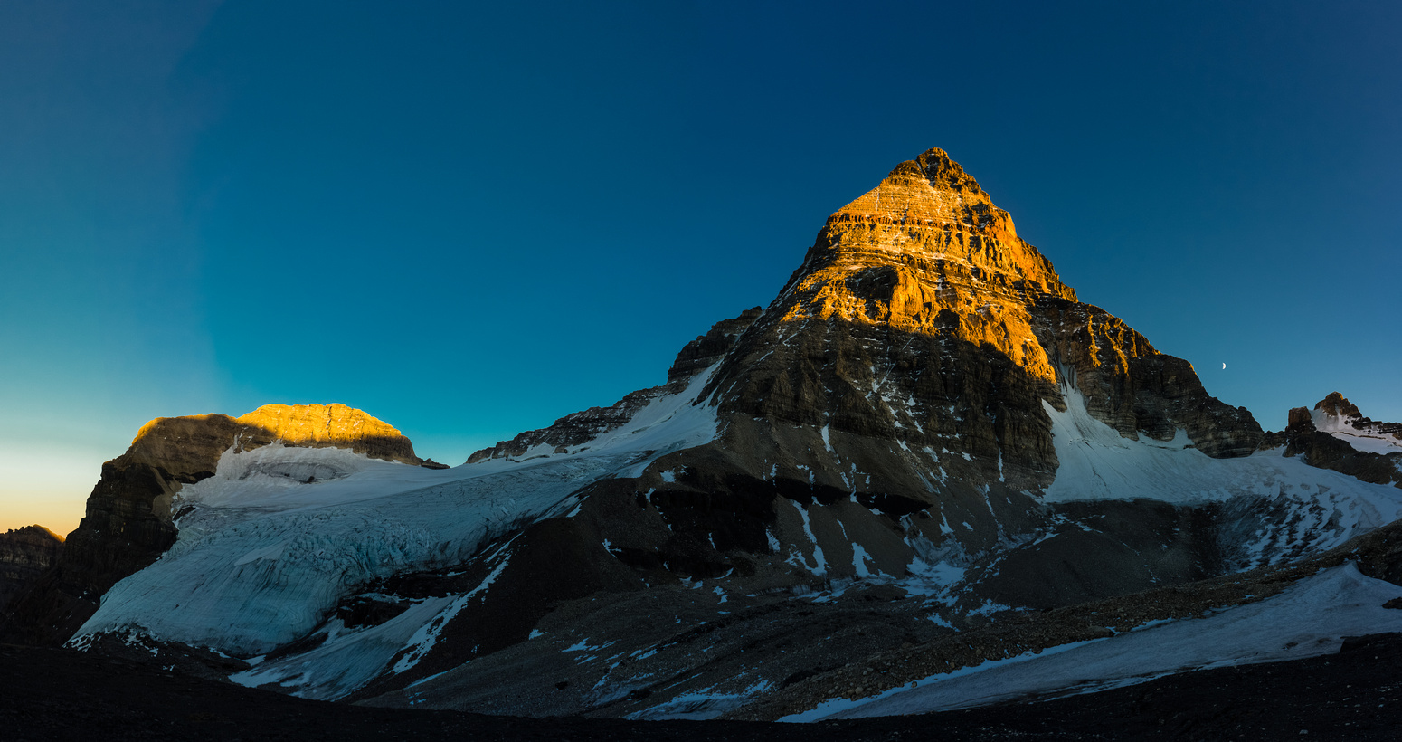 Mount Assiniboine with the moon as the sun sets. Our route goes up the ridge trending to skyline left from bottom left.