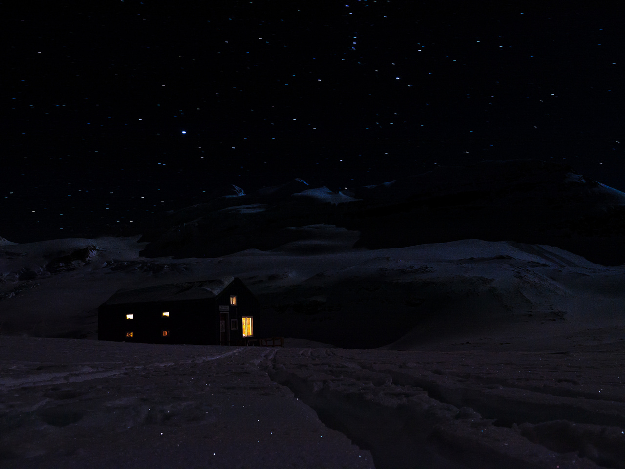 A cheery hut under a star-filled cold winter sky.