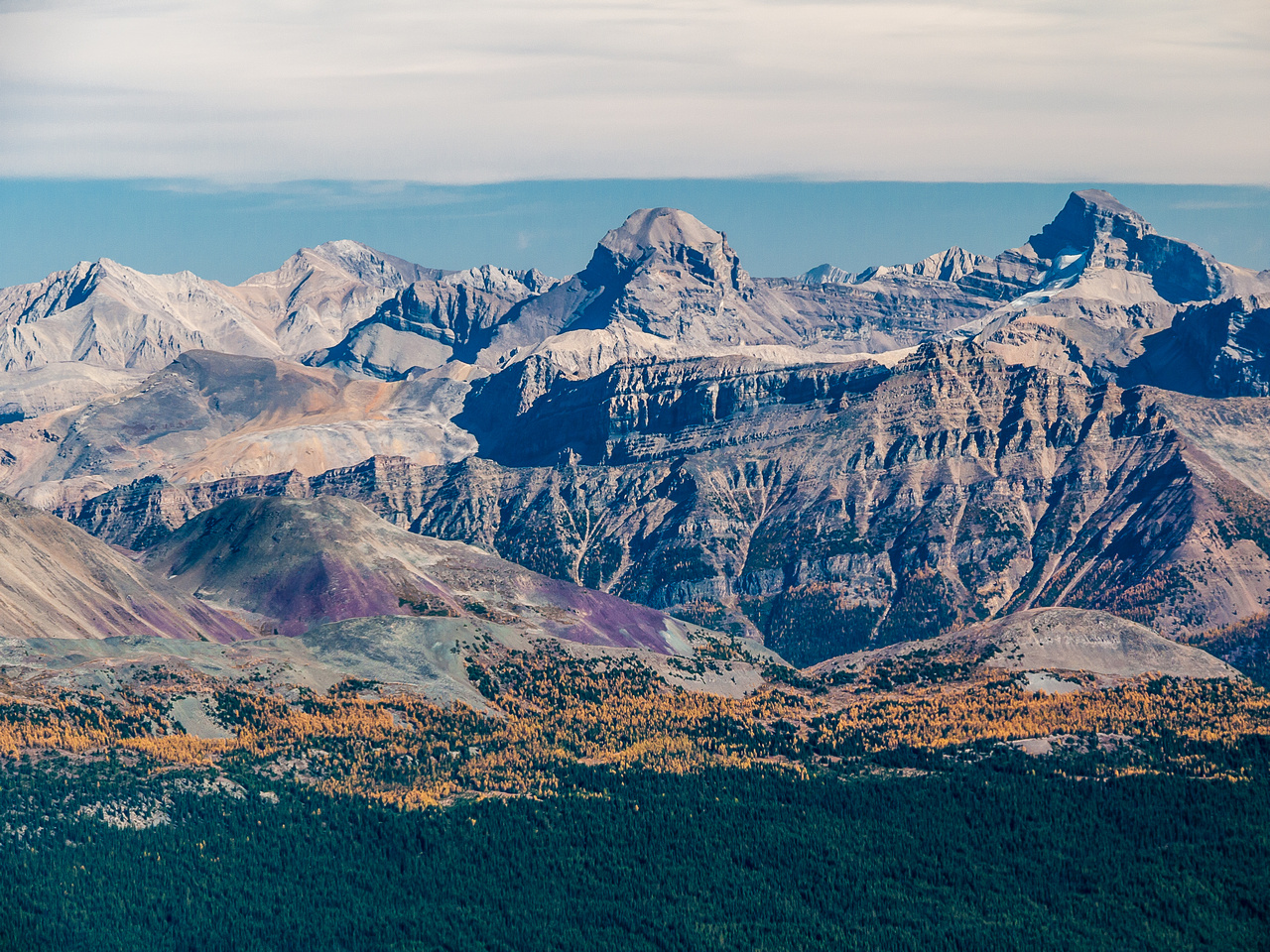 Skoki peaks including Douglas and St. Bride with brightly colored larches and purple scree.