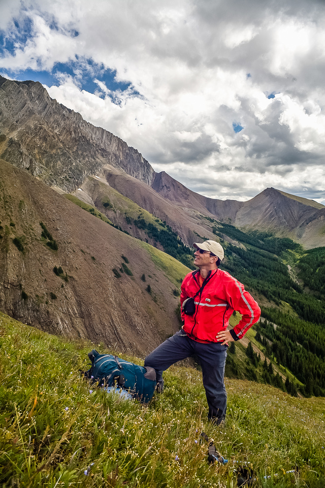 Keith looks back at our route down the west face before we plunge down grassy slopes to the creek below.