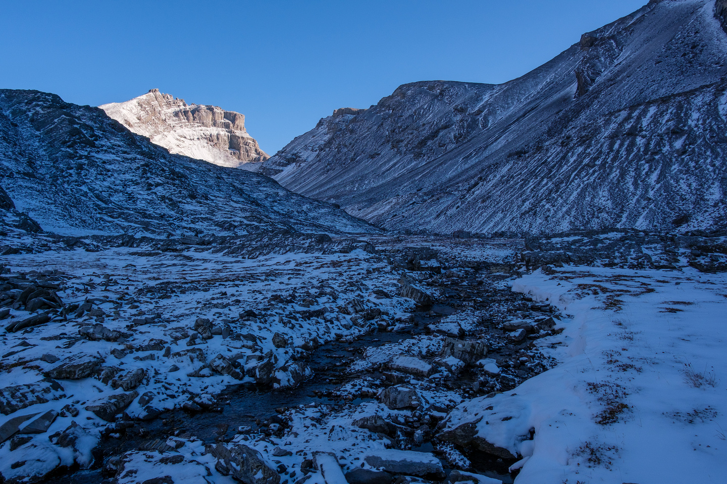 Hiking above the Headwall Lakes. The Fortress in sun with the South Outlier to the right.
