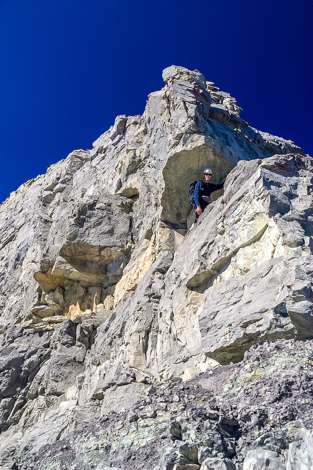 JW traverses climber's right under a small roof while climbing the crux.