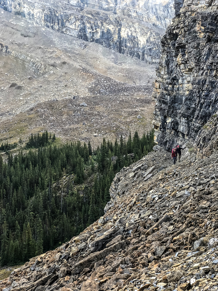 Traversing a goat path along cliffs to the west to avoid wet bushwhacking.