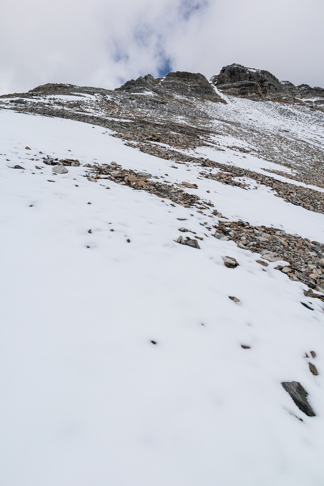 The summit is still a few hundred vertical meters from the col.