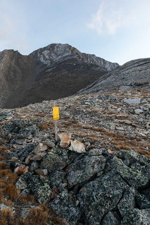 A Banff National Park boundary marker with the summit of Carrot Peak above.