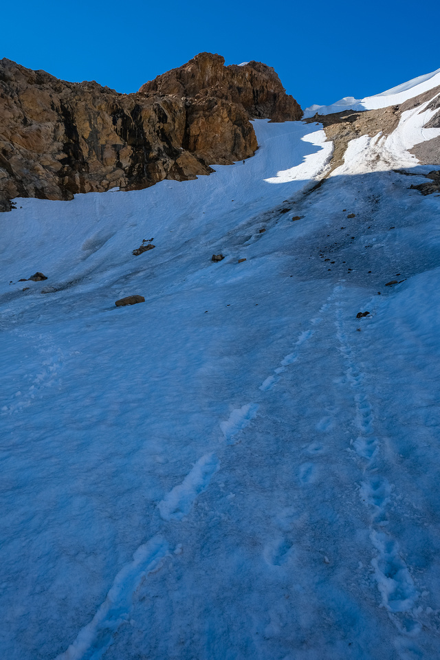 Phil is a tiny dot on the huge snow slope leading to the scree ledges above.