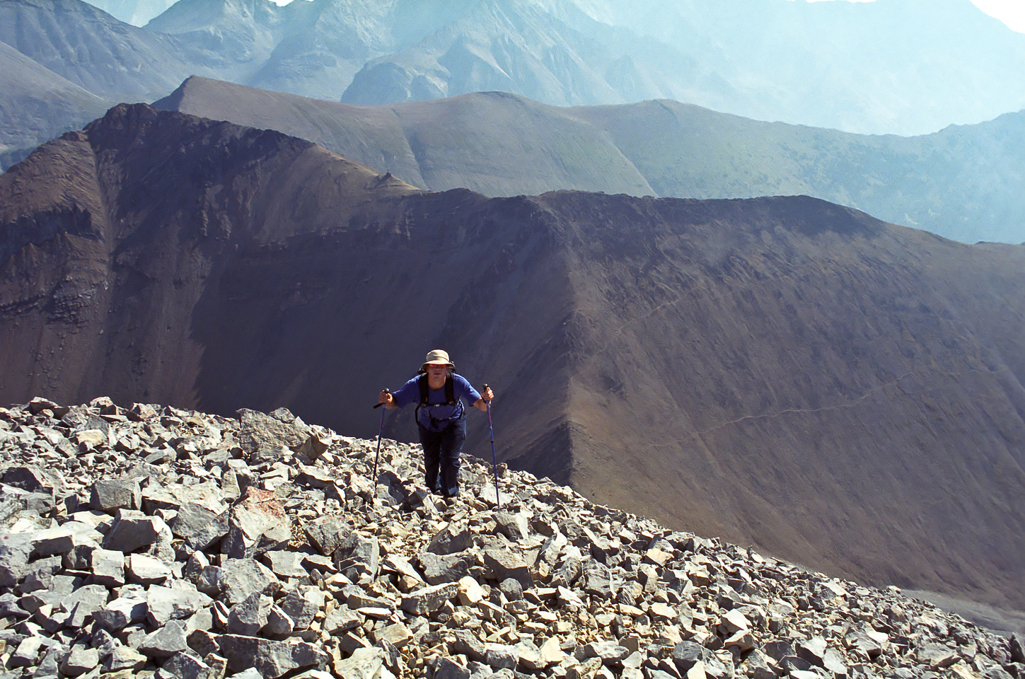 Kev comes up to the summit on classic Rockies scree with Grizzly and Highwood Ridge in the background.