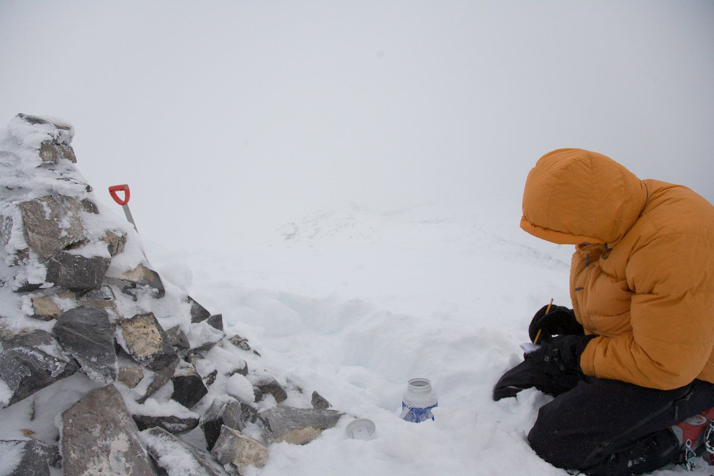 Jason struggles against the cold as he scribbles something in the summit register.