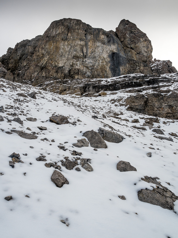 The scree ledge traverse is obvious under the impregnable cliffs above.