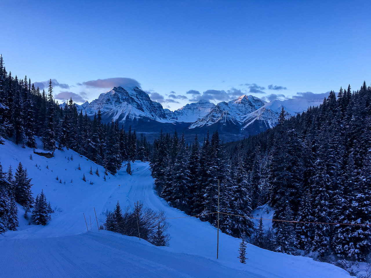 Gorgeous early morning light on the Lake Louise peaks, including Mount Temple, seen from the first steep section on the Lake Louise ski-out.