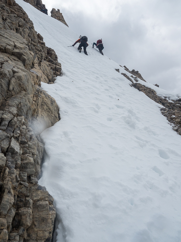 Carefully downclimbing the steep snow slope - remember that nobody else has crampons.