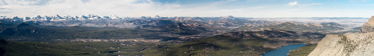 A distant panorama from the Flathead Range on the left to the Livingstone Range just right of center and the prairies at far right.
