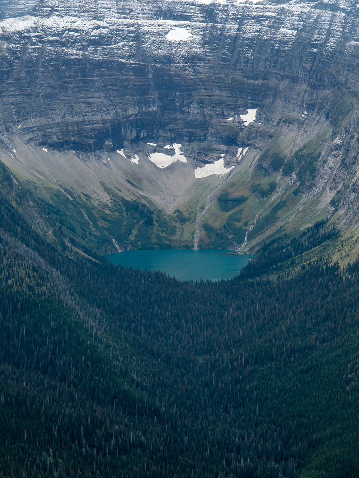 The lower steep walls of Chapman Peak rise over Carcajou Lake.