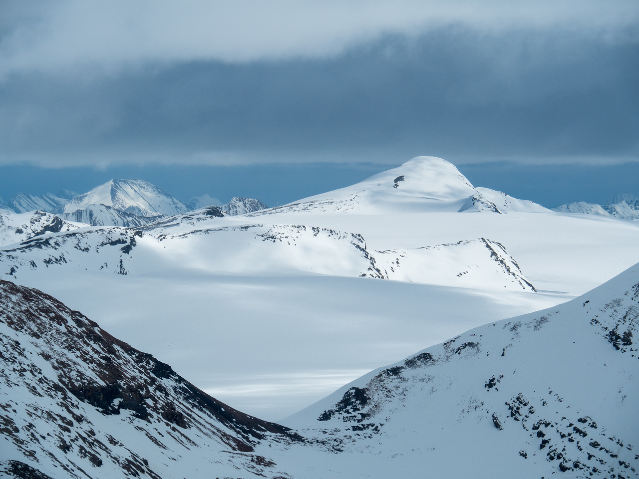 An unnamed snowy peak on the Reef Icefield. Snowbird Pass at lower foreground at center.