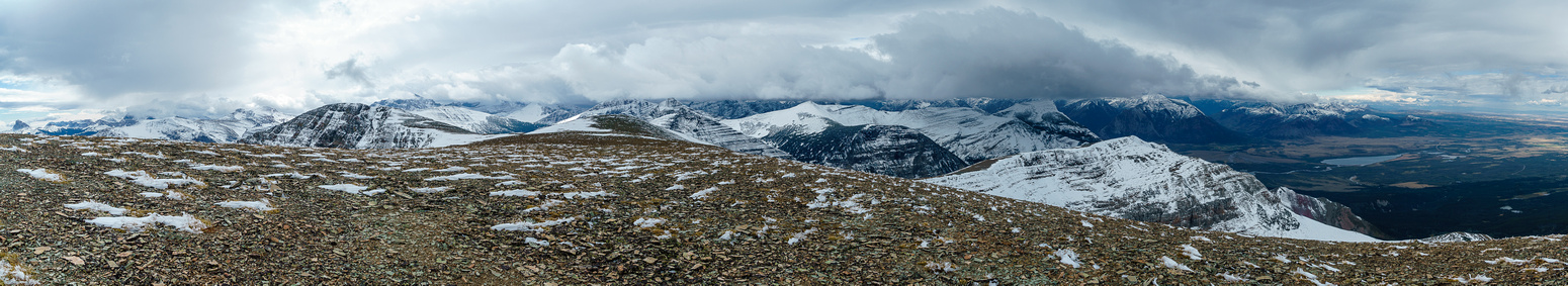 After cresting the moderate terrain, the summit is at far left with threatening clouds over the park at center.