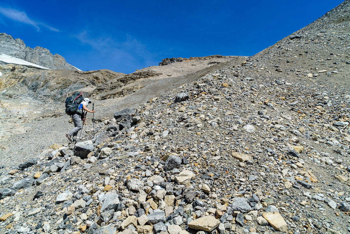 Ben grunts up the loose scree / moraines beneath the high col.