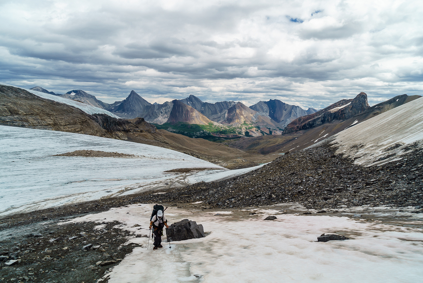 Finally off the glacier, climbing up a snow patch to the moraine above the rocky bivy coral.