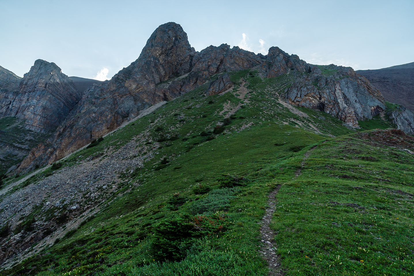 """Arriving at an upper grassy bench which was the only relief from the steep grade, just before the ascent through the """"gates"""" visible above."""