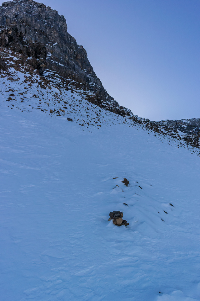The tracks end. Boo. Note the cairn and the faint sign of a buried track in the scree underneath the snow cover.