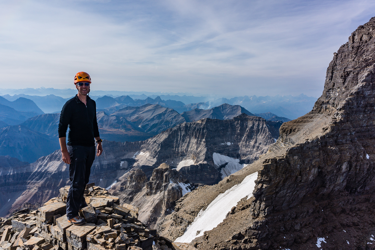 Vern on the summit of Lunette Peak. Assiniboine's SW face and east face to the right.