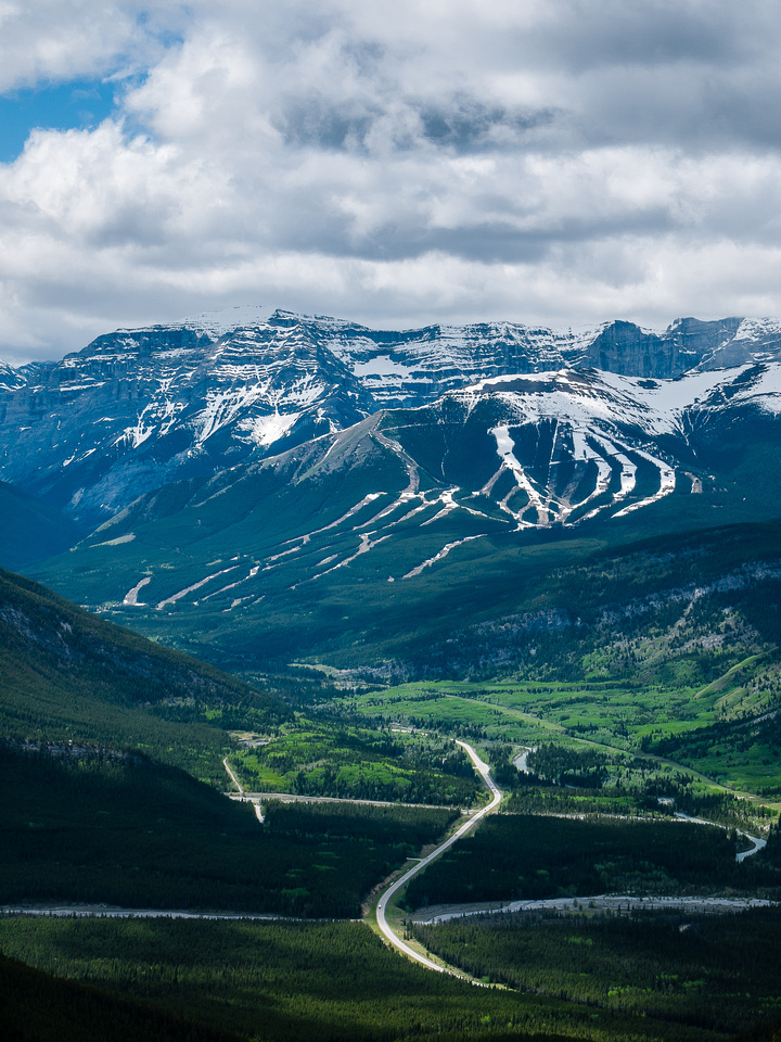 Green Spring in the valley bottom with snow on the Nakiska ski hill above.