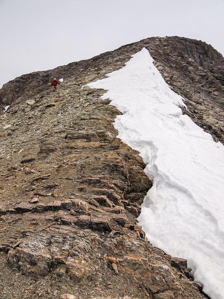 Bill comes off the summit plateau to the mouth of the descent gully.
