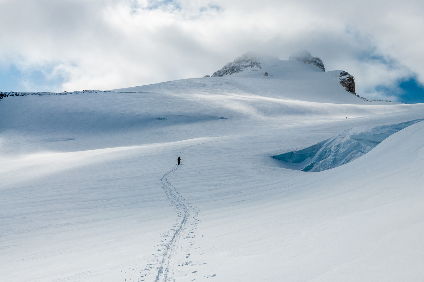 Skiing past a large crevasse on the Hector Glacier with the summit above and the two French guys clearly visible now.