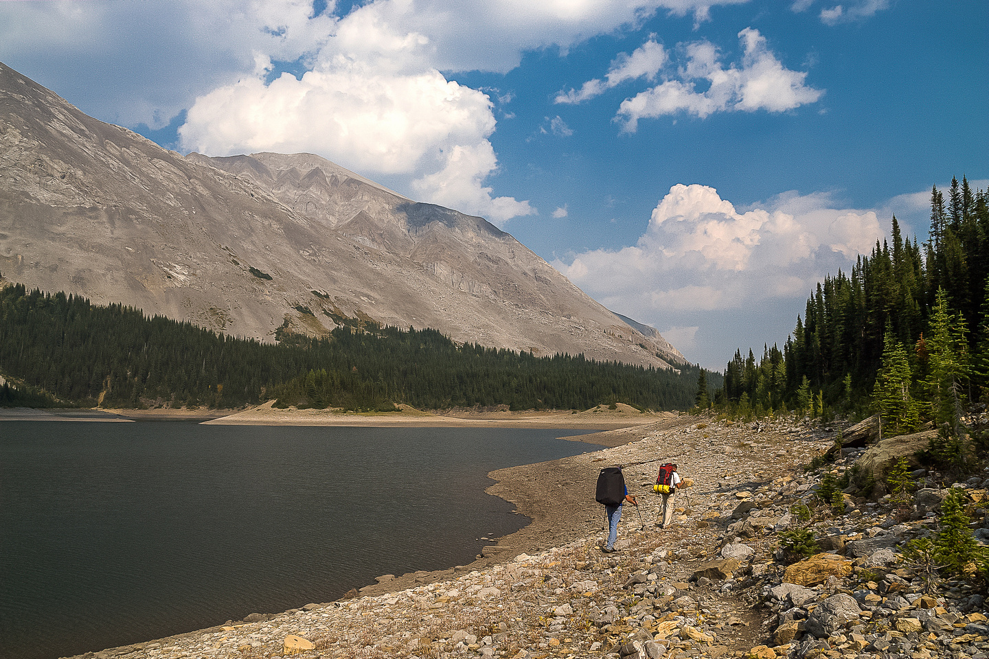 Hiking along Three Isle Lake to our campsite which is located on the left side in the distance around the shoreline. Mount Putnik rises on the left.