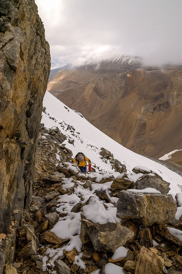 Under thick cloud, Bob scrambles up through the rubble and cliff bands on Kiwetinok Peak.