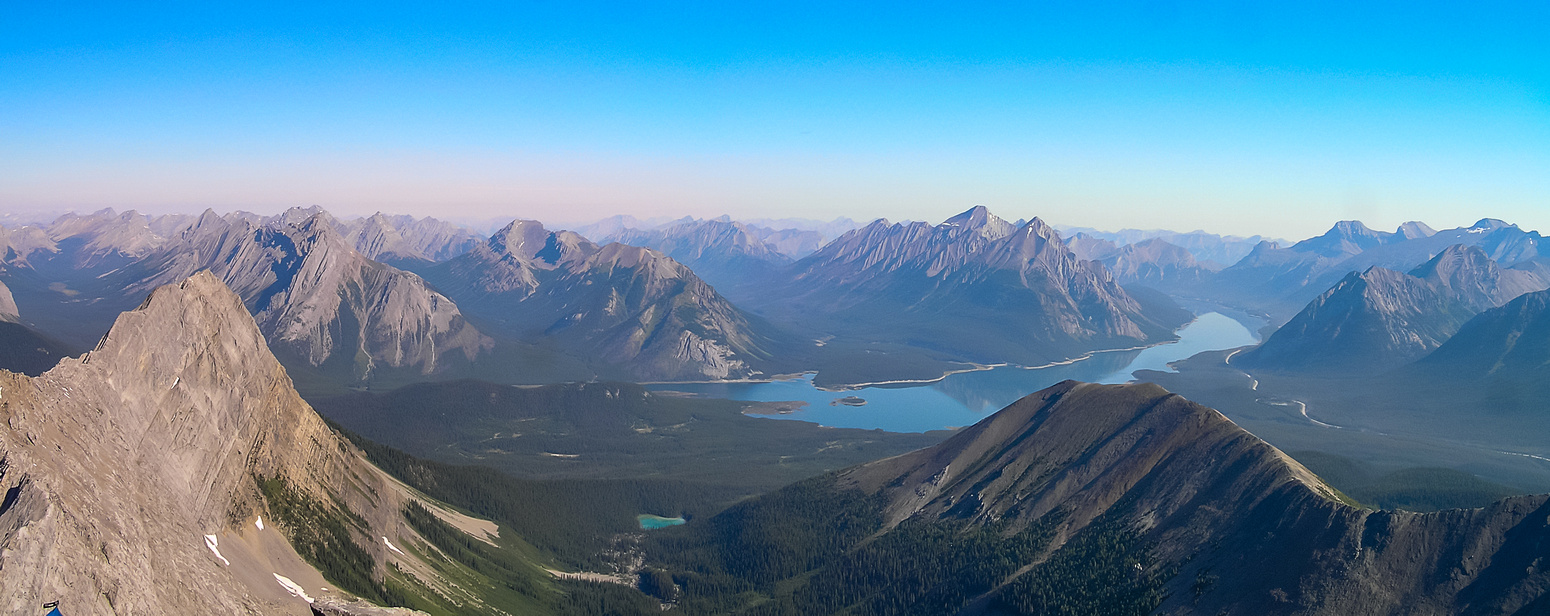 A glass-smooth Spray Lakes with Mount Shark (L) and Tent Ridge (R) in the foreground and Fortune and Nestor beyond.