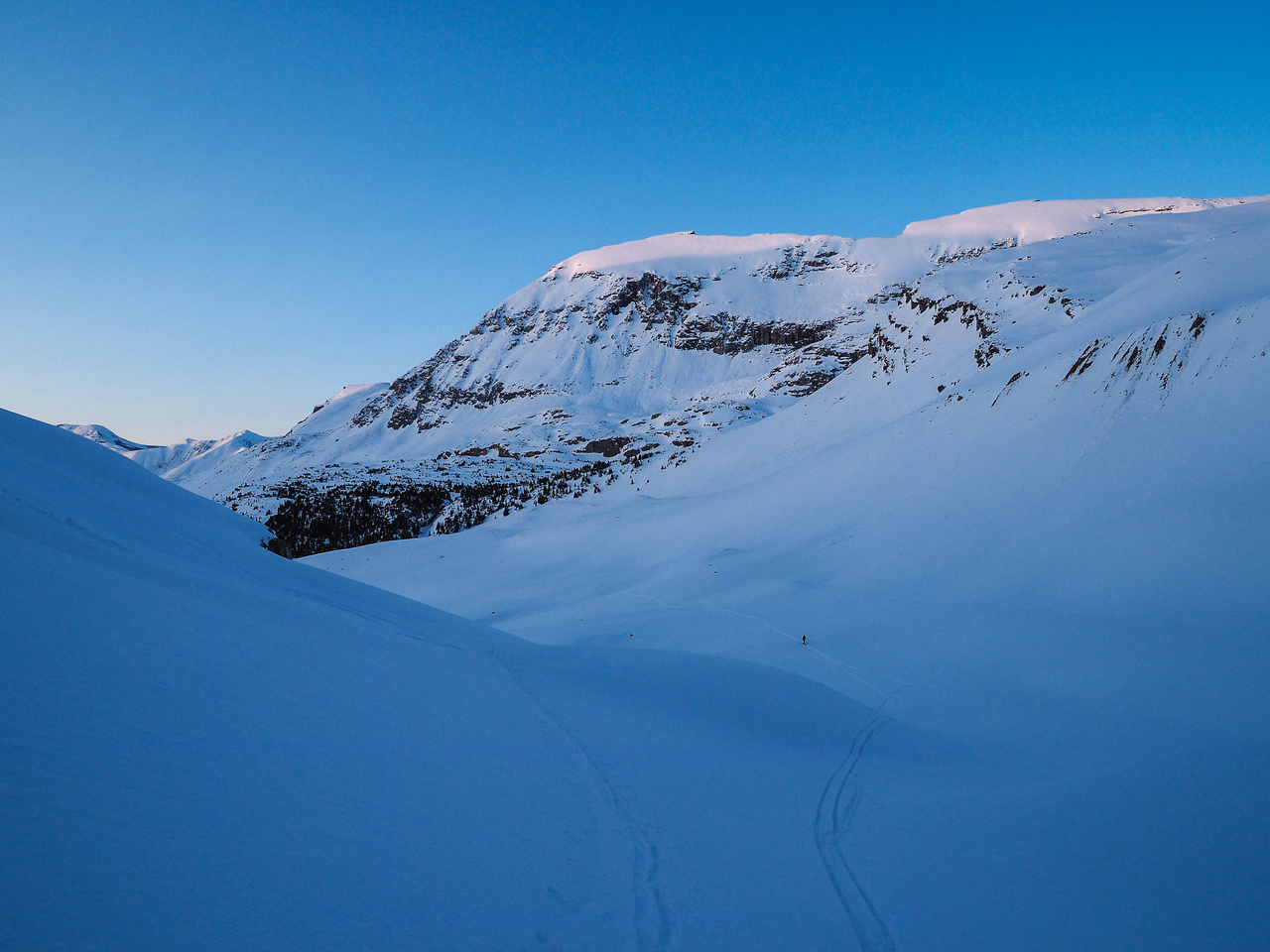 The sun starts setting as we work our way up the steep headwall below the hut.